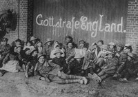 British Soldiers At A Picnic Party With French Children In A Newly Recaptured Village Beneath An Inscription Left By The Germans